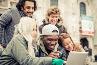 friends looking at ipad travel city ipad treasure hunt concept
