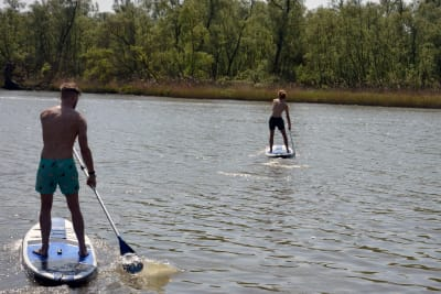 two men doing stand up paddle boarding on lake