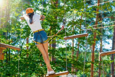 woman climbing high ropes