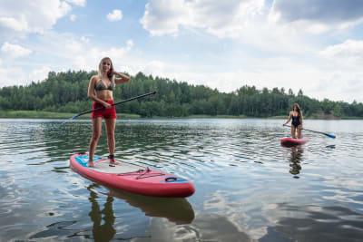 two women paddle boarding in lake in Latvia