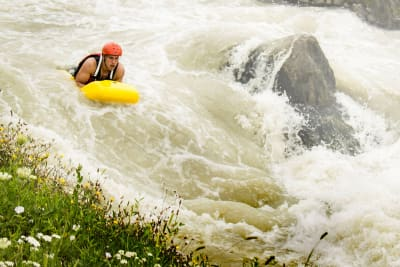 A man going down the rapids on a hydro speed
