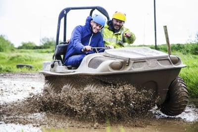 men on an argocat with mud splashing everywhere