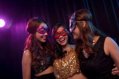 three women having un at a masquerade ball