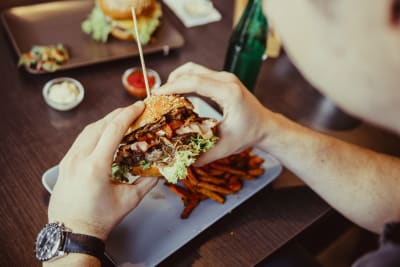 A man holds a burger