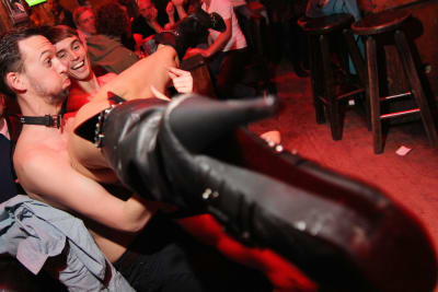 A man with a stripper on his lap during a strip dinner