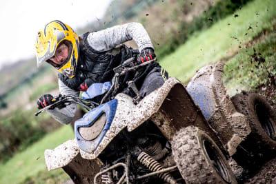 A muddy man on a quad bike