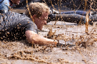 A man crawling through mud on assault course