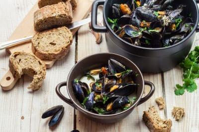 a bowl of mussels with bread