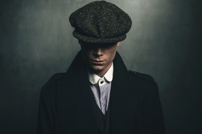 Peaky Blinders tour portrait of retro 1920s english gangster with flat cap