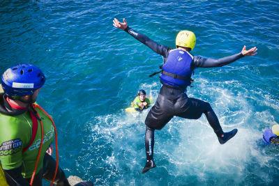 man jumping from cliff coasteering