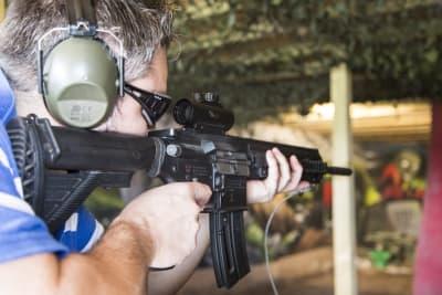 A man shooting an assault rifle