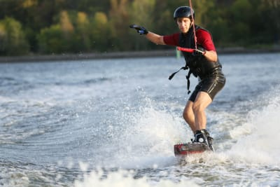 wake boarder doing wake boarding on a cable
