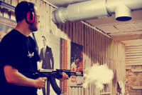 A man shooting a machine gun AK47