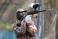 A man fires a a paintball gun