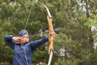 Person shooting bow and arrow in archery