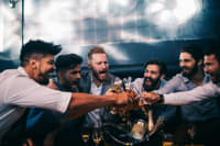 Group of men toasting a beer at a nightclub
