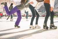 three young people enjoying ice skating