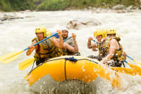 a group of happy people white water rafting