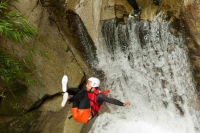 A man jumps from a cliff durning canyoning activity