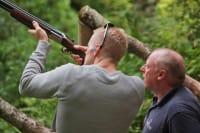 a man shooting a shotgun