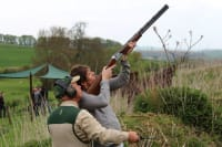 A man shoots a shotgun during clay pigeon shoot