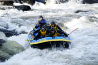 A stag party travel down rapids white water rafting