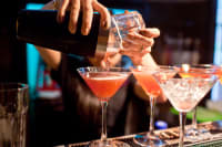 A man pours cocktails ata bar