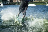 A man on a wakeboard pulled by a cable tow