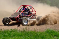 a man races around a muddy track in a rage buggy