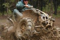 A man drives a quad through the mud