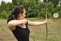 A woman shooting a bow and arrow