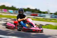 A group of guys racing go karts on a stag weekend